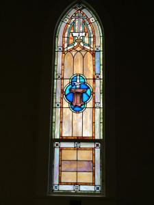 A stained glass depiction of the Holy Spirit descending like a dove in baptism at First Lutheran Church in Poulsbo, Washington