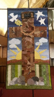 A cross that is lifted on a banner that is lifted up.